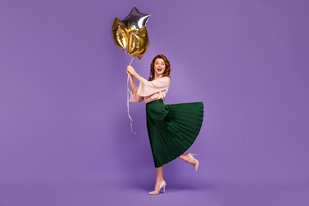 Полноразмерное фото довольной привлекательной девушки, держащей воздушные шары в форме звезды