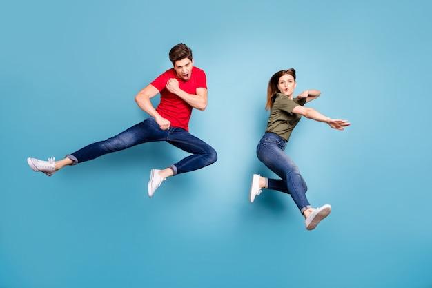 Полноразмерная фотография двух людей сумасшедших в стиле фанк успешной супружеской пары ниндзя прыжок практики боевых боевых упражнений носить зеленую красную футболку современный наряд, изолированные на синем цветном фоне