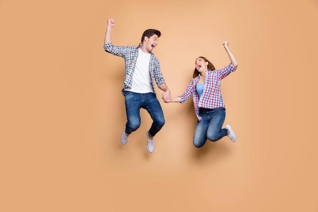 Полноразмерная фотография двух человек сумасшедшая леди парень прыгает высоко, празднуя лучшую победу, поднимая кулаки, распродажа, делая покупки, держась за руки, носить повседневную клетчатую джинсовую одежду, изолированный бежевый фон