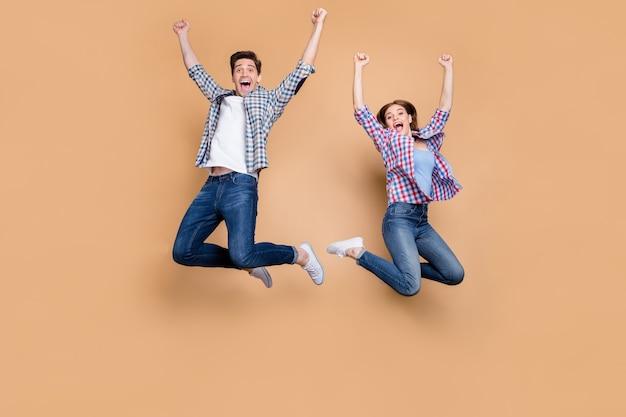Полноразмерная фотография двух людей, сумасшедшая леди, прыгающая высоко, празднуя лучшую победу, поднимающую кулаки, распродажа, торговые новости, повседневная джинсовая одежда в клетку, изолированный бежевый цвет