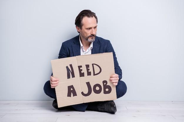 Полноразмерная фотография несчастного напряженного работника зрелого парня из-за финансового кризиса потеряла работу, удерживая картонный плакат, искать работу, сидя на полу, смотреть сбоку, носить синий костюм, туфли, изолированные на сером фоне