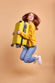 動揺した女性の観光客のジャンプハグ黄色のスーツケースのフルサイズの写真は、パステルイエロー色の背景、肖像画の上に分離された国の国境を離れて旅行空港をお楽しみください。旅行、休暇の概念