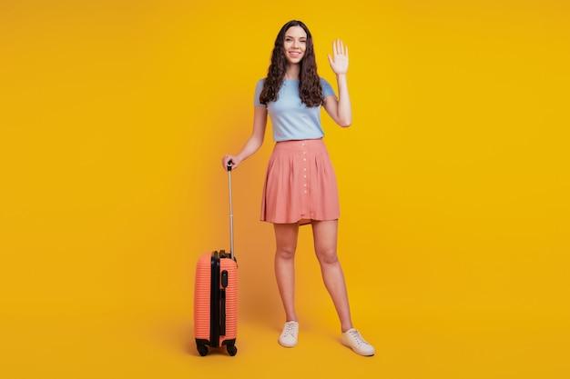 若い魅力的な女性の幸せなポジティブな笑顔のバッグスーツケースのフルサイズの写真は、黄色の背景に分離されたこんにちはを振っています