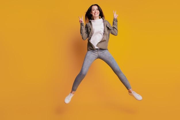 노란색 배경에 격리된 젊은 부주의한 여성 점프 쇼 v-sign의 전체 크기 사진
