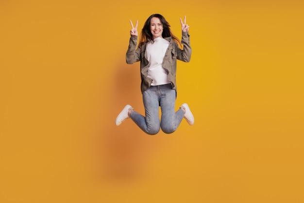 노란색 배경에 격리된 젊은 쾌활한 여성 점프 쇼 v-sign의 전체 크기 사진