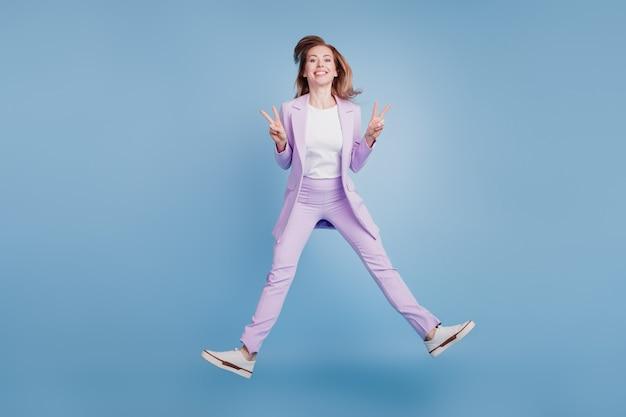 파란색 배경 위에 격리된 어린 소녀 점프 쇼 v-sign의 전체 크기 사진