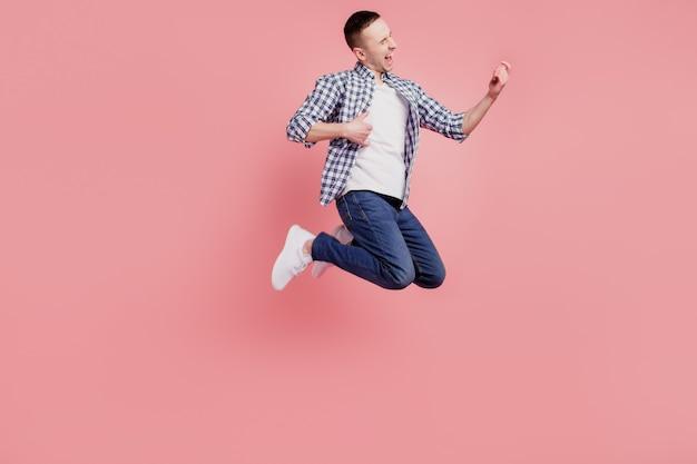 ピンク色の背景で隔離の若い男の幸せなポジティブな笑顔ジャンプ興奮したプレイギターのフルサイズの写真