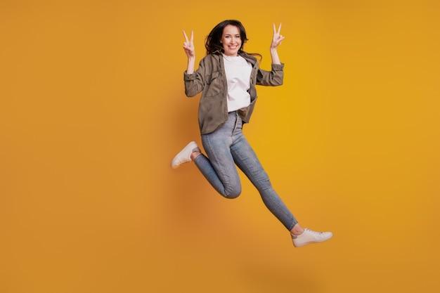 노란색 배경에 격리된 젊은 긍정적인 여성 점프 쇼 v-sign의 전체 크기 사진