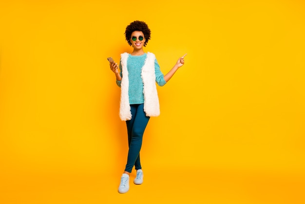 Full size photo positive afro american girl use smartphone browse promo point finger copyspace wear blue pants trousers teal jumper white vest stylish trendy isolated yellow color wall