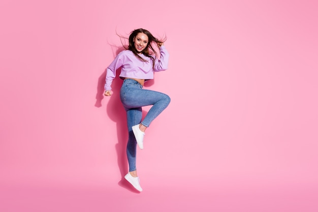 Full size photo of positive cheerful girl enjoy rejoice discount lottery win jump raise fists scream yes wear style stylish pullover isolated over pastel color background