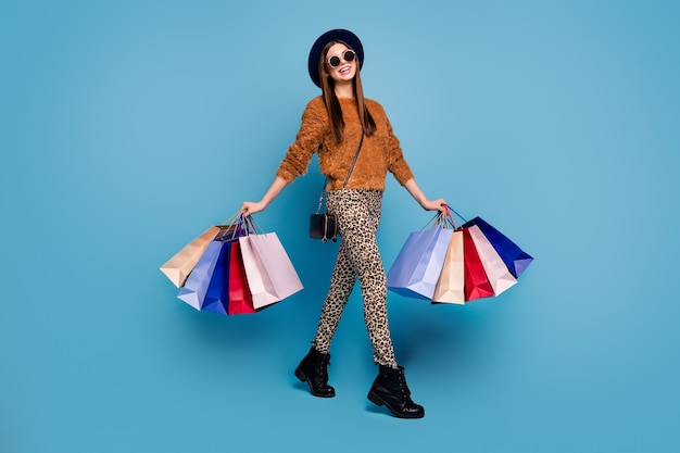 Full size photo of positive emotions girl tourist have shopping weekends hold many bags look good wear autumn fall winter brown sweater trousers clutch isolated blue color wall