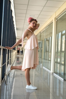 Full size photo of romantic woman posing in corridor wearing pink dress
