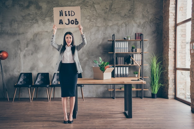 Full size photo of stressed depressed girl have problem with job search lose occupation crisis company bankrupt show cardboard text wear suit high-heels in workplace workstation