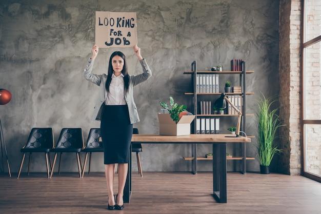 Full size photo of upset girl banker economist hold cardboard text look for job lose company bankrupt wear blazer jacket suit high-heels in workplace workstation