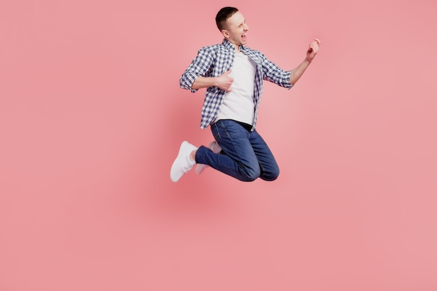 Full size photo of young guy happy positive smile jump excited play gitar isolated on pink color background