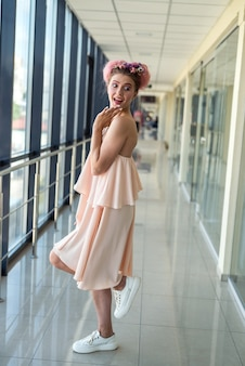 Full size photo of young woman in pink dress with flowers