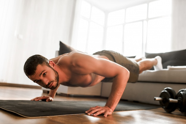 Full size picture of t-shirtless guy sportsman stand in plank position throwing legs on the sofa alone in room.