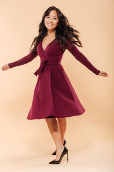 Full size portrait of charming asian female in pretty maroon dress dancing and looking on camera being isolated over beige background
