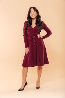 Ritratto a grandezza naturale della femmina asiatica affascinante in vestito marrone rossiccio grazioso che posa sopra il fondo beige con il sorriso brillante e la mano sulla vita