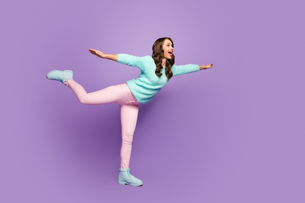 Full size portrait of excited cheerful woman enjoy free time rest raise hands legs imagine she swallow fly air sky wear good look pastel sweater.