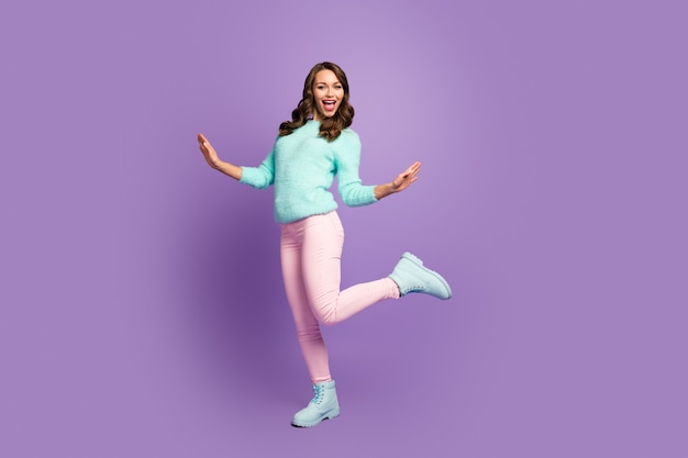 Full size portrait of excited crazy funky girl enjoy weekends moving wear good look pastel jumper footwear.