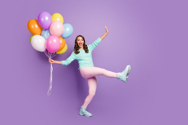 Full size portrait of funny feminine girl enjoy occasion celebrate her friends anniversary hold many air baloons scream wear pastel soft trend boots.