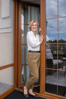 개인 주택의 출입구에 서 있는 웃고 있는 만족스러운 사랑스러운 성숙한 세련된 여성의 실물 크기 초상화