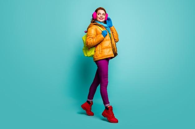 쾌활한 꿈꾸는 여자의 전체 크기 초상화는 겨울 강의를 걸어 가방을 착용하십시오. 노란색 분홍색 보라색 빨간색 녹색 점퍼 복장.
