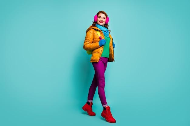 사랑스러운 귀여운 여자 대학생의 전체 크기 초상화는 밝은 배낭 모양의 좋은 착용 녹색 점퍼 빨간색 파란색 신발을 잡아 도보로 이동합니다.