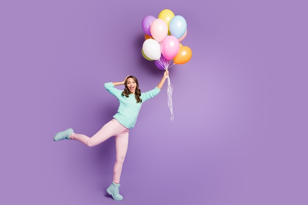 Full size portrait of surprised feminine girl get present many baloons flying sky she catch impressed scream wow omg wear pink pants trousers pastel turquoise jumper.