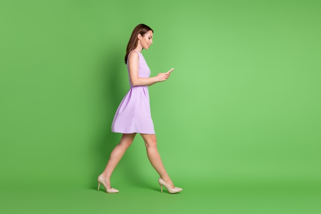 Full size profile photo of adorable pretty lovely young girl lady go empty space look telephone type chat blogging free communication wear purple dress isolated pastel green color background