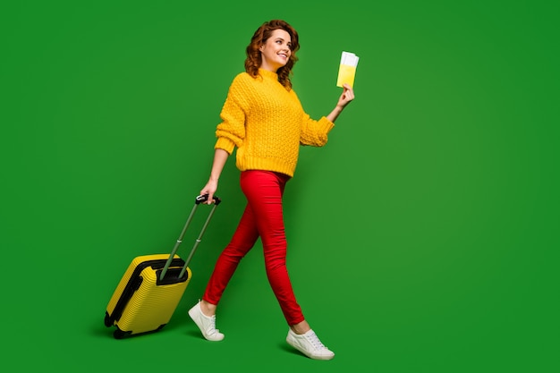 Full size profile photo of cheerful lady hold tickets passport travel abroad rolling case go flight registration table wear yellow sweater red pants shoes isolated green color wall