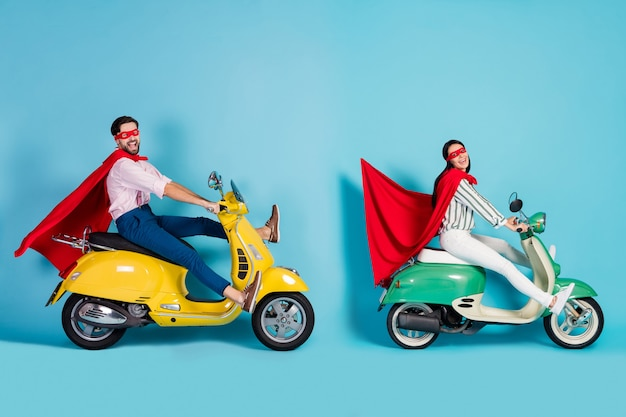 Full size profile photo of excited lady guy drive two retro moped big speed brakes stop wear red cape mask play party super hero role coat fly air isolated blue color wall