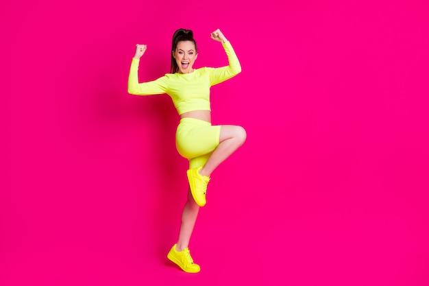 놀란 섹시한 젊은 여성의 전체 크기 프로필 사진은 활기찬 핑크색 배경에 격리된 드레스 스포츠 슈트 신발을 주먹으로 들고 서 있습니다.