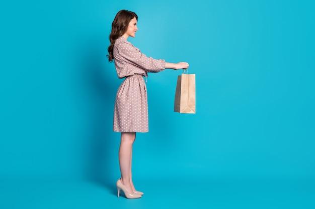 美しい魅力的な女性のフルサイズのプロフィール写真は、紙袋を保持し、ボーイフレンドにロマンチックなサプライズウェアドットドレススティレット分離された青い色の背景を与える食品配達サービスを購入します
