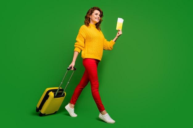 Полноразмерная фотография профиля веселой дамы с билетами для паспорта путешествия за границу на колесиках иди на рейс регистрации в таблице носить желтый свитер красные брюки туфли изолированы зеленая цветная стена