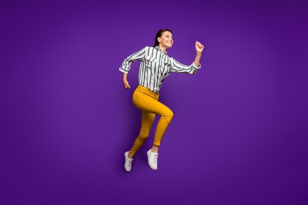 Полноразмерное фото профиля сумасшедшей красивой женщины, прыгающей высоко, спешащей к финишу, конкурентоспособной спортсменки в полосатой рубашке, желтых брюках, изолированного фиолетового цвета фона