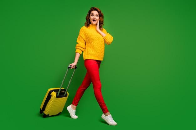 Полноразмерная фотография профиля возбужденной женщины, катящей чемодан, пойти на регистрацию рейса, изменить билет авиакомпании на бизнес-класс, носить желтый свитер, красные брюки, туфли, изолированные на стене зеленого цвета