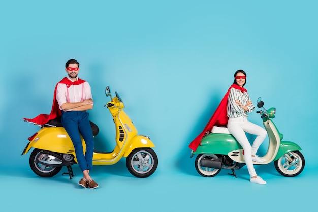 재미 있은 여자 남자 팔의 전체 크기 프로필 사진 두 빈티지 오토바이 착용 빨간 케이프 마스크 할로윈 파티 플레이 슈퍼 영웅 역할 격리 된 파란색 벽에 대 한 준비가 앉아 넘어