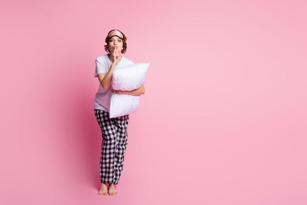 面白い女性のフルサイズのプロフィール写真はピンクの壁に枕の指の唇を保持します