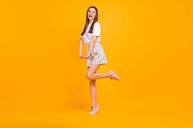 Полноразмерная фотография профиля смешной дамы, идущей по улице, наслаждается солнечным днем, кокетливая одежда, повседневная белая футболка, полосатые шорты, туфли, изолированные на стене яркого желтого цвета