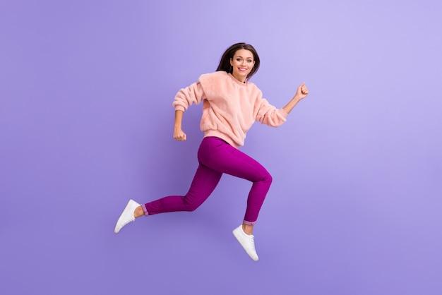 보라색 벽에 높은 착용 캐주얼 옷을 점프하는 여자의 전체 크기 프로필 사진