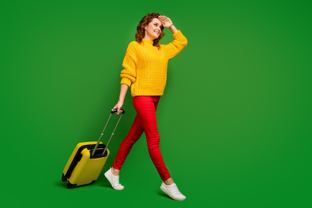 Полноразмерная фотография профиля красивой дамы на колесиках с чемоданом иди на регистрацию, смотри подальше, рука, помогай скрыть глаза от солнечного света, носить желтый свитер красные брюки туфли изолированы зеленая стена
