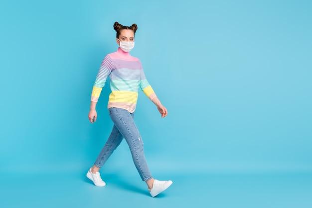 예쁜 10대 여성의 전체 크기 프로필 사진은 사회적 거리를 유지하며 거리 검역 시간을 착용하고 얼굴 마스크 청바지 줄무늬 풀오버 신발을 격리된 파란색 배경을 보호합니다.