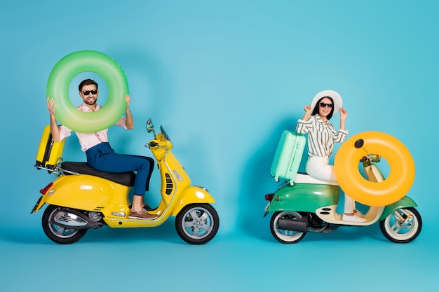 Full size profile photo of positive two people bikers riders driver drive choppers travel summer weekends carry bags luggage yellow green life rubber buoy isolated over blue color wall