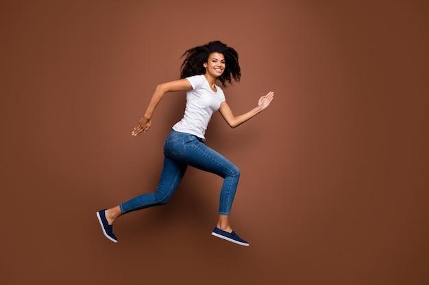 결승선 승자 분위기를 서두르는 높은 스포츠 대회 점프 놀라운 어두운 피부 아가씨의 전체 크기 프로필 초상화 캐주얼 흰색 티셔츠 청바지를 착용하십시오.