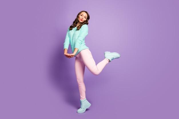 공기를 보내는 꽤 재밌는 물결 모양의 여성의 전체 크기 프로필 초상화는 로맨스 무드를 시시덕 거리는 인상 다리 착용 푹신한 풀오버 핑크 파스텔 바지 신발을 착용합니다.