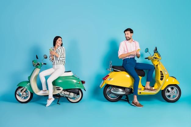 전체 크기 프로필 측면 사진 미친 놀란 두 사람이 자전거 운전자 앉아 노란색 녹색 모터 자전거 사용 스마트 폰 감동 gps지도 비명 omg 절연 파란색 벽
