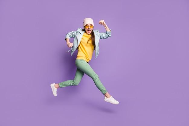 Полноразмерная боковая фотография изумленной возбужденной девушки, наслаждающейся лотерейной скидкой, выигрывающей прыжок, бегом, быстрой скоростью, надетой на зеленые штаны, головные уборы, солнцезащитные очки, изолированные на фиолетовом фоне