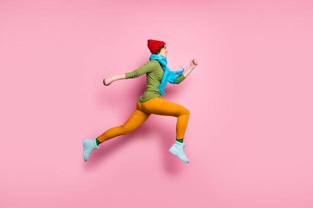 Полноразмерное фото сбоку веселой очаровательной девушки, вскакивающей на бег после весенних скидок, носите туфли, красный синий свитер, штаны, головные уборы, изолированные на стене розового цвета